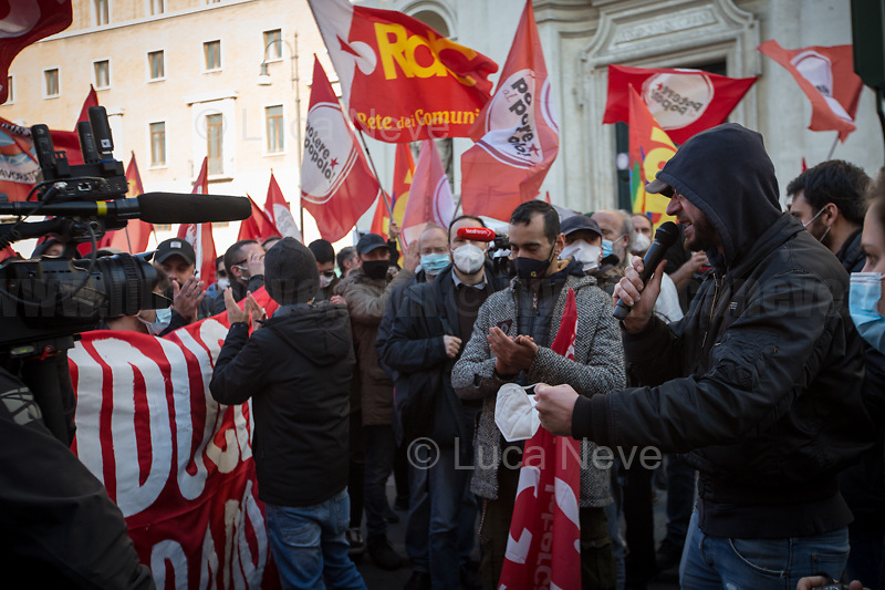 Rome, Italy. 18th Feb 2021. Today, the Trade Union Si Cobas, Potere Al Popolo Party, Rifondazione Comunista Party and other organizations of the non-parliamentarian Left held a rally (1.) in Piazza San Silvestro to protest against the new Italian Government led by the former President of the European Central Bank, BCE, Professor Mario Draghi (2. 3.). From the organisers Facebook event page: «[…] We call to mobilize male and female workers, the unemployed, the precarious, the students, the popular classes and all the associations and people who struggle, who do not want to stand by while a government that is directed expression of a united bosses front is ready to strike us with anti-people policies. It is time to join the fight against the government of banks and bosses: we will not pay for this crisis! […]». The demo ended peacefully, even though there were moments of tension between protesters and full riot gears police officers due to demonstrators aimed to march to the Parliament.<br /> <br /> Footnotes & Links:<br /> 1. https://www.facebook.com/events/4966336456769715<br /> 2. 13.02.2021 - Mario Draghi's New Italian Government Swears At Quirinale Palace http://bit.do/fNPQ5<br /> 3. 17.02.2021 - Italian Prime Minister Mario Draghi Arrives at Italian Senate http://bit.do/fNPRc