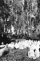 Ethiopia. West Gujam. Danbecha district. Anjeni is a small village. On sunday morning after the orthodox mass service, the women dressed with white loinclothes and veils seat on the ground outside the church near the cemetary and talk together. © 1996 Didier Ruef