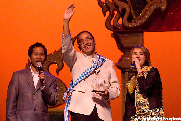 Bryan Thao Worra, center, is presented with an award by Aloun Khotisene and Ketsana Vilaylack during the first annual Lao Artists Festival in Elgin, IL on August 21, 2010.  (photo by Khampha Bouaphanh)