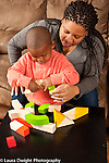 Two year old toddler boy with mother twisting turning block after mother showed him how it works