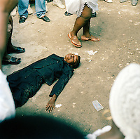 A local woman worshipping at a Haitain Voodoo ceremony. It is believed spirits possess the worshippers and speak through them. Port-Au-Prince, Haiti