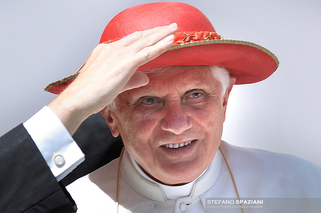 """George Gaenswein secretary of the Pope helps Pope Benedict XVI wear his """"saturno"""" hat before the weekly general audience on June 16, 2010 in St Peter's square at the Vatican."""