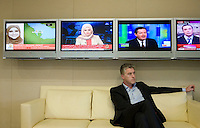 Al Anstey, Managing Director of Al Jazeera English in his office in Doha, with television screens showing different news channels behind.