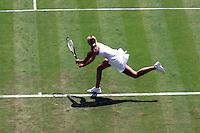 Woman running after a ball on a grass tennis court