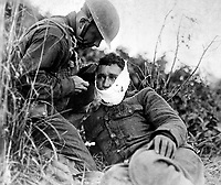 Soldier of Company K, 110th Regt. Infantry (formerly 3rd and 10th Inf., Pennsylvania National Guard), just wounded, receiving first-aid treatment from a comrade.  Varennes-en-Argonne, France.  September 26, 1918.  Lt. Adrian C. Duff. (Army)<br /> NARA FILE #:  111-SC-24719<br /> WAR & CONFLICT #:  669