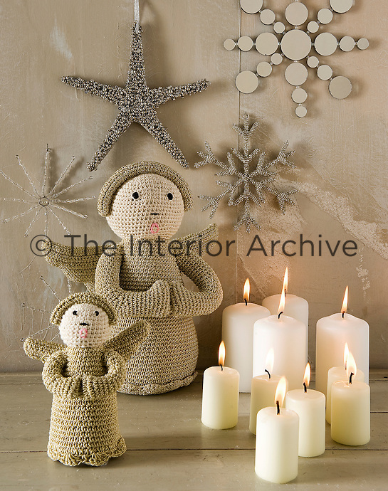 Detail of a Christmas still life with a pair of woven angels and group of candles next to a wall decorated with beaded stars and snowflakes