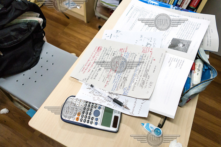 Home work left on a desk during a meal break at the Shanghai High School, one of the most exclusive and demanding in the country. Its students academic day often run from 06:45 to as late as 21:00.