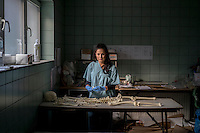 Victoria Amina-Dautovic, a staff member at an International Commission on Missing Persons (ICMP) mortuary facility, trains using a synthetic skeleton.