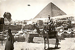 A vintage photograph of Egypt shows a UFO in the sky above the pyramid