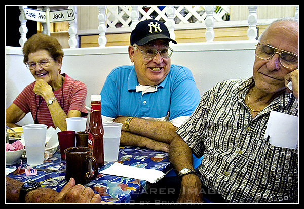 """Long-time Key West residents Rose Einhorn, left, and Lenny Salazar, right, react to yet another corny one-liner delivered by Chippy Fernandez, center, at the breakfast table at Dennis Pharmacy in Key West, Florida on July 19, 2006.  The pharmacy, origin of Jimmy Buffet's famed """"Paradise Cheeseburger,"""" is finally closing its doors after 44 years in business. (Brian Ray for Key West Magazine)"""