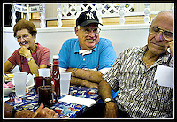 "Long-time Key West residents Rose Einhorn, left, and Lenny Salazar, right, react to yet another corny one-liner delivered by Chippy Fernandez, center, at the breakfast table at Dennis Pharmacy in Key West, Florida on July 19, 2006.  The pharmacy, origin of Jimmy Buffet's famed ""Paradise Cheeseburger,"" is finally closing its doors after 44 years in business. (Brian Ray for Key West Magazine)"