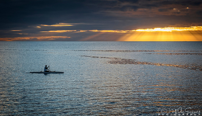 A lone canoeist paddles during sunset off the coast of Niue in the Pacific Islands.