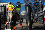 Workers install barbed wire on fencing infant of the U.S. Capitol ahead of President-Elect Joe Biden's Inauguration on January 19, 2021 in Washington, D.C..  Photograph by Michael Nagle