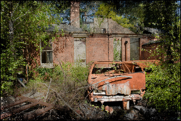 Rusted car in front of abandoned building