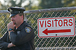 Menomonee Falls police officer at a fenced gate with a visitors sign and arrow pointed at police officer.