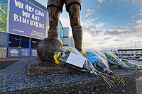 Pictured: Flowers and tributes left by the statue of Frederick Charles Keenor outside the Cardiff City Stadium in south Wales, UK. Tuesday 22 January 2019<br /> Re: Premier League footballer Emiliano Sala was on a flight which disappeared between France and Cardiff.<br /> The Argentine striker was one of two people on board the Piper Malibu, which disappeared off Alderney on Monday night.<br /> Cardiff City FC, signed the 28-year-old from French club Nantes.<br /> A search is under way.<br /> A Cardiff Airport spokeswoman confirmed the aircraft was due to arrive from Nantes but said there were no further details.<br /> HM Coastguard has sent two helicopters to help.