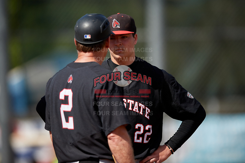 Ball State Cardinals starting pitcher Chayce McDermott (22) talks with head coach Rich Maloney (2) during a game against the Saint Joseph's Hawks on March 9, 2019 at North Charlotte Regional Park in Port Charlotte, Florida.  Ball State defeated Saint Joseph's 7-5.  (Mike Janes/Four Seam Images)
