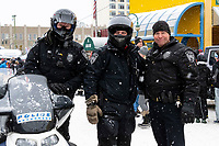 Anchorage police officers pose before heading at on the trail at 4th Avenue and D street in downtown Anchorage, Alaska on Saturday March 7th during the 2020 Iditarod race. Photo copyright by Cathy Hart Photography.com