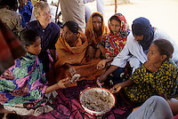 Near Bankilare, southwestern Niger - Tuareg Women at Lunch of Rice and Meat.  The American woman is present to inquire about Guinea Worm eradication efforts.  It is still common for many Tuaregs to eat with their hands from a common bowl.