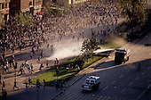 """Santiago, Chile<br /> October 1988<br /> <br /> After General Pinochet lost a vote to remain in office, hundreds battle police demanding his immediate removal.<br /> <br /> In October 1988, General Augusto Pinochet ordered a plebiscite vote asking Chilean citizens whether he should continue in office. It produced a decisive """"no"""" vote and the following year he lost the first presidential election in 19 years. However, under a constitution crafted by his advisors, he remained as army commander until 1998. <br /> <br /> Pinochet continued to wield enormous power until his arrest in London on human rights charges in October 1998."""