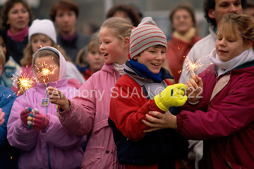 Lichterfelde, Berlin (West) and Teltow, Potsdam (East) crossing post, West Germany<br /> November 14, 1989 <br /> <br /> West German children celebrate the opening of the Berlin Wall with sparklers. Germans gathered as the wall is dismantled and the East German government lifts travel and emigration restrictions to the West on November 9, 1989.
