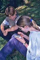 Fifth grade students looking at rock with hand lens. Oregon.