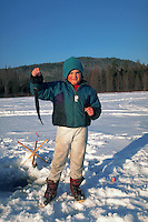Young boy holding up the fish he caught while ice fishing.