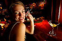 """Party goers try the """"e-cig"""" at Temple Bar in New York City.  The e-cig is a chinese made device that mimics the act of smoking and can be smoked legally indoors."""