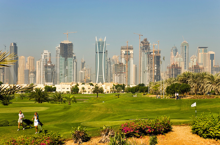 Dubai.  Skyline of Emirates Lakes Towers, Dubai Marina and Jumeirah Beach Residences overlooks the Montgomerie Golf Course at Emirates Hills.  Villa developments..