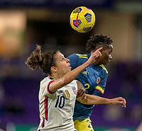 ORLANDO, FL - JANUARY 18: Carli Lloyd #10 of the USWNT heads the ball away from Kelly Ibarguen #2 of Colombia during a game between Colombia and USWNT at Exploria Stadium on January 18, 2021 in Orlando, Florida.