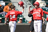Nebraska Cornhusker Kale Kiser (14) is greeted by Cody Asche (22) after scoring in the first inning against Texas on Sunday March 21st, 2100 at UFCU Dish-Falk Field in Austin, Texas.  (Photo by Andrew Woolley / Four Seam Images)