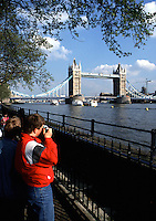 Tourists snap pictures of the Tower Bridge and River Thames. London, England.