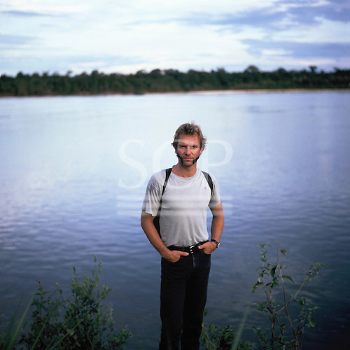 Xingu River, Brazil. Sting with intricate face paint standing on the shores of the Xingu River.