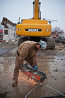 Workers demolish a closed car wash at the corner of a parking lot where Wal-Mart will build a new store in a strip shopping center in Westerville, OH. Here a worker collects copper wire for recycling.