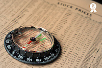 Compass on stockmarket cotation in newspaper, studio shot (Licence this image exclusively with Getty: http://www.gettyimages.com/detail/sb10068805l-001 )