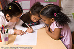 Education Preschool 3-4 year olds two girls watching another girl write her name on class sigh-in sheet horizontal