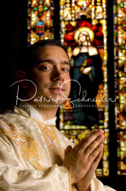Portrait of a Catholic Priest in front of stained glass inside of the Basilica at Belmont Abbey  in Belmont, NC.