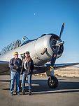 Brenda Heinz with Chet Stringham and his  North American Aviation NA-64 Yale WWII-vintage airplane at the Winnemucca, Nev. airport, subject for an early morning photo session with M.d. Welsh at Shooting The West XXX.<br /> <br /> <br /> #ShootingTheWest XXX, #WinnemuccaNevada, #NA-64Yale, #Aviation