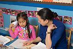 Afterschool homework help program for Headstart graduates Grades K-3 female teacher working on math with girl