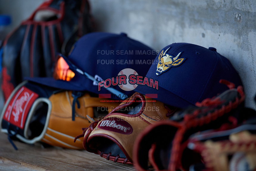 State College Spikes hat and gloves on the bench during a NY-Penn League game against the Mahoning Valley Scrappers on August 29, 2019 at Eastwood Field in Niles, Ohio.  State College defeated Mahoning Valley 8-1.  (Mike Janes/Four Seam Images)
