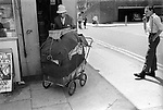 Tower Hamlets east London. Skinhead boy or bovver boy in braces and boots looks on at man with his belongings stacked into a pram. 1978.<br /> <br /> Danny Holloway, is the bovver boy, and is now a chef in Sweden. Thanks to Wayne Waterson.<br /> <br /> My ref 3/3570/,1978,