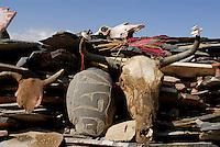 Shrine with yak skulls, colored barley and mani, or prayer stones carved with Buddhist mantra Om Mani Padme Hum, on the pilgrim circuit, or kora, around the monastery walls of Sera Monastery, Lhasa, Tibet, China.