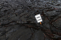 """Road buried in lava rock from the eruption of Kilauea, with a """"road closed"""" sign, on the Hawaii Big Island"""