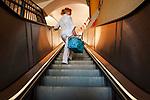 Deutschland, Bayern, Chiemgau, Traunstein: junge Frau mit Einkaufstasche auf einer Rolltreppe - aufwaerts | Germany, Bavaria, Chiemgau, Traunstein: young woman with shopping bag on an escalator - upwards