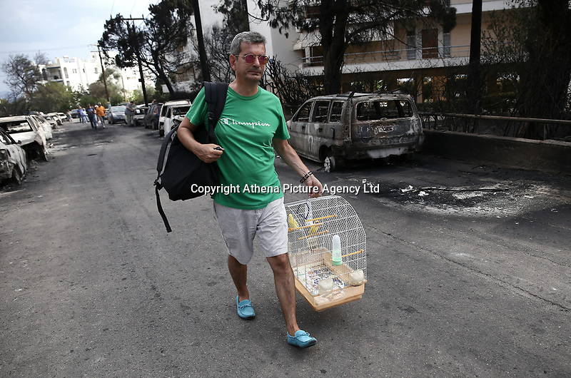 Pictured: A lacal man leaves with his pet bird following the aftermath of the forest fire which has claimed dozens of lives in the Mati area of Rafina, Greece. Tuesday 24 July 2018<br /> Re: Deaths caused by wild forest fires throughout Greece.