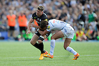 Owen Farrell of Saracens is hit by Henry Slade of Exeter Chiefs after he has passed the ball