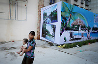 A woman and her child walk past an advertisement for a new holiday resort. Major coastal developments have been one of the major causes of mangrove loss in Zhanjiang, Guangdong Province. Over the past century, the world has lost over 50% of its coastal mangroves. They have been cleared mainly to make way for commercial shrimp and fish farms. The unique trees which live in salt water are valued for the ability to protect shorelines and are home to a diverse array of flora and fauna. 2010