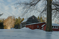 Barns reflection shows from the ice covered layers of deep snow one March evening at sunset.