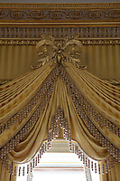 Detail of the ornately carved centrepiece holding up swags of curtain made of the same matching fabric as the walls