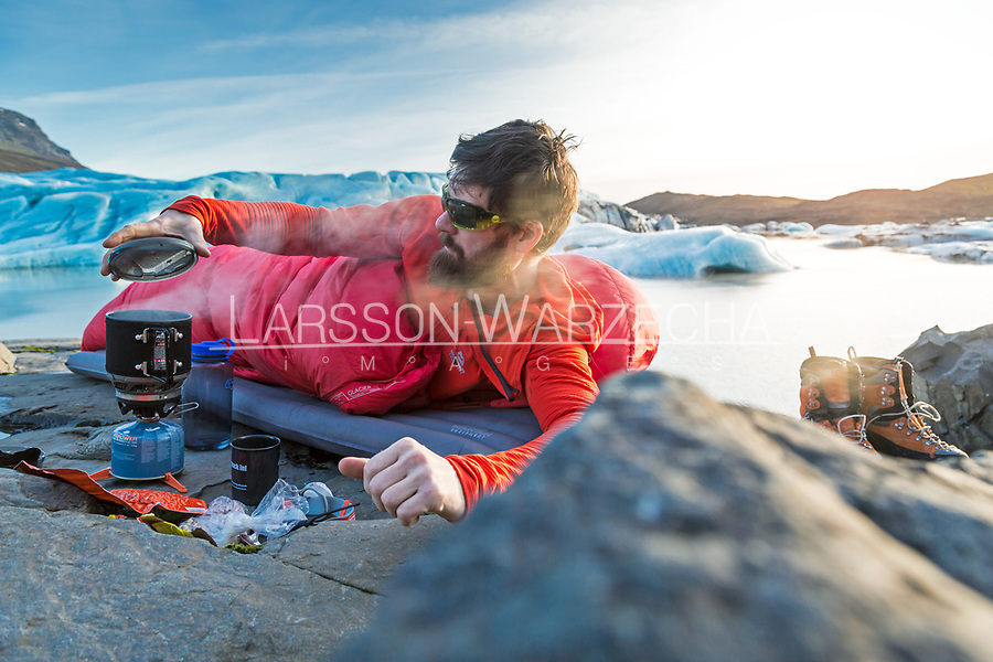 Male hiker wild camping beside a glacier, Iceland